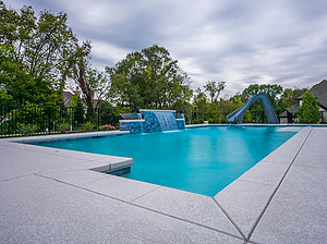 st louis pool construction, custom concrete pool, geometric, raised wall, sheer descent, water slide, textured deck