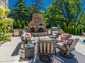 st. louis pool construction, wooden outdoor furniture with plush tan cushions, fireplace