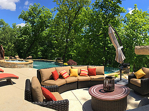 st. louis pool construction, brown wicker outdoor furniture with tan cushions, red and yellow pillows