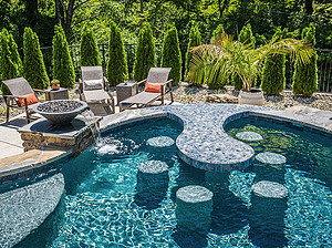 st. louis custom designed concrete pool with fire bowls, water bowls and lounge furniture, concrete bar and stools inside of pool