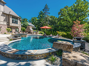 freeform st. louis custom designed concrete pool with raised wall, fire bowls, diving rock and outdoor kitchen