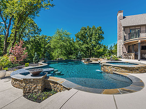 freeform st. louis custom designed concrete pool with flagstone coping, fire bowls, spa and exposed pool wall