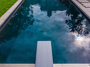 geometric st. louis custom designed concrete pool with diving board and stepping stone pathway