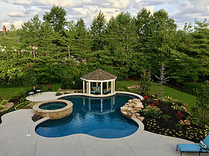 freeform st. louis custom designed concrete pool with spa, gazebo, rock waterfall and colorful landscaping