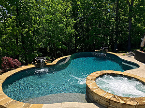 freeform st. louis custom designed concrete pool with fire bowls, water bowls, spa and vanishing edge