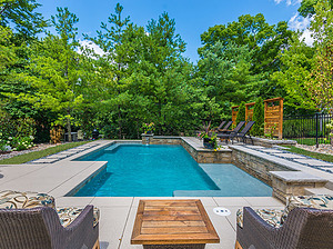 st. louis custom designed concrete pool with stepping stone pathway and multiple seating areas