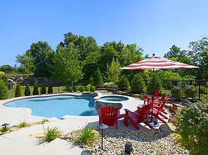 st. louis custom designed concrete pool with spa and red patio furniture