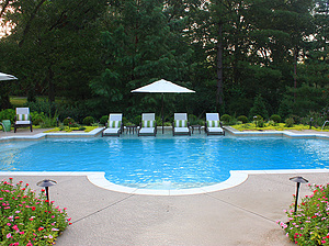 symmetrical st. louis custom designed concrete pool with geometric shape and white lounge chairs