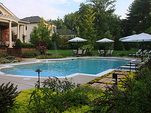 symmetrical st. louis custom designed concrete pool with geometric shape and white furniture and umbrellas