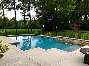 st. louis custom designed concrete pool with exposed wall and tiki torches