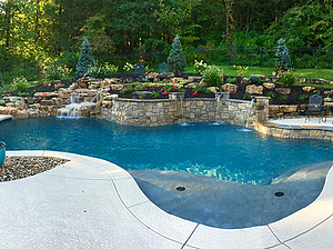 freeform st. louis custom designed concrete pool with raised pool wall and waterfall, heavily landscaped