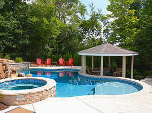 freeform st. louis custom designed concrete pool with spa, gazebo and red patio furniture