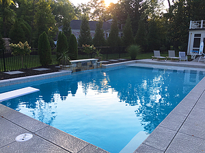 sun setting on rectangular st. louis custom designed concrete pool with diving board