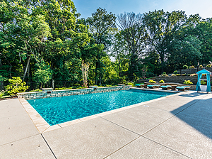rectangular st. louis custom designed concrete pool with raised pool wall, scuppers and teal furniture