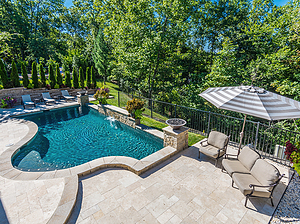 st. louis custom designed concrete pool with fire bowls, retaining wall, natural privacy screen and patio furniture