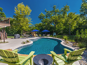 freeform st. louis custom designed concrete pool with basketball hoop and green patio furniture