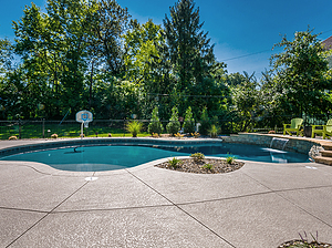 freeform st. louis custom designed concrete pool with basketball hoop, sheer descent and green patio furniture