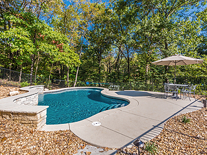 freeform st. louis custom designed concrete pool with raised wall and surrounded by gravel