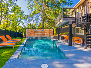 geometric st. louis custom designed concrete pool with sheer descent, wooden privacy fence and yellow patio furniture and lounge chairs