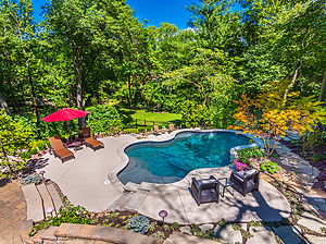 sunken patio with freeform st. louis custom designed concrete pool, heavily wooded surroundings