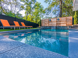 geometric st. louis custom designed concrete pool with wooden privacy fence and yellow lounge chairs