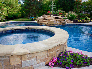 st. louis custom designed concrete pool, raised concrete spa with stone veneer and flagstone coping
