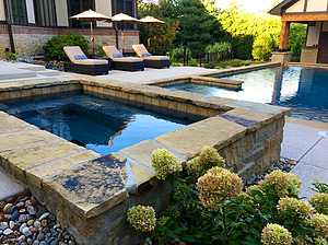 st. louis custom designed concrete pool, stand alone rectangular raised concrete spa with stone veneer and flagstone coping