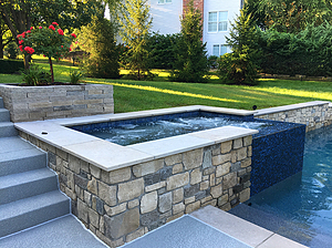 st. louis custom designed concrete pool, raised rectangular concrete spa with stone veneer and blue tile