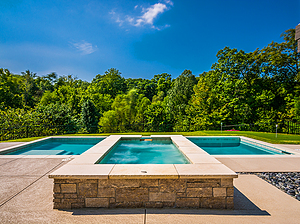st. louis custom designed concrete pool, raised rectangular concrete spa with stone veneer and flagstone coping