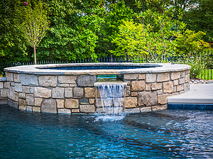 st. louis custom designed concrete pool, raised concrete spa with spillway, stone veneer and flagstone coping
